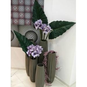Вазы с зелеными листьями и фиолетовым амариллисом